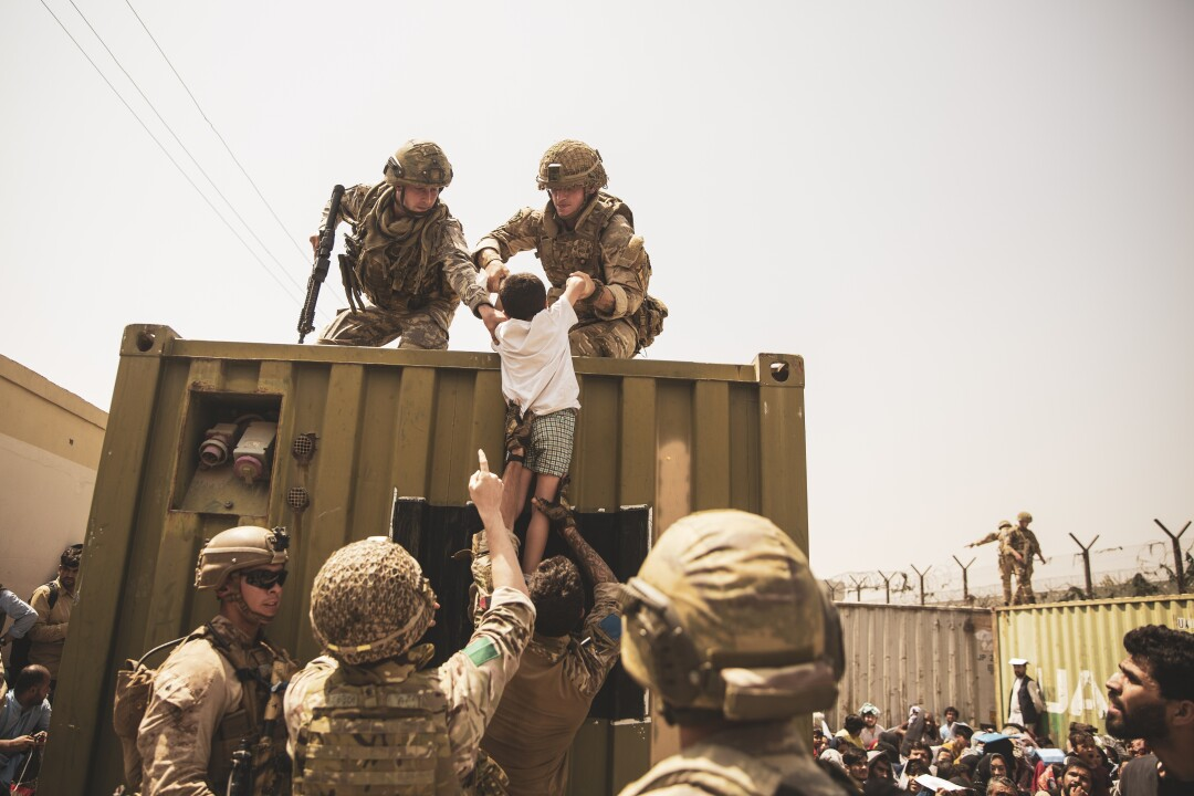 British and Turkish coalition forces, along with U.S. Marines, assist a child during an evacuation