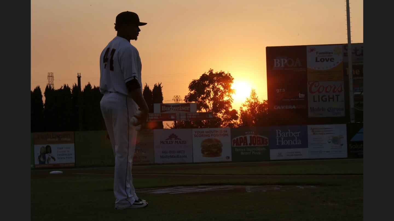 The sun slowly sets over Sam Lynn Ballpark beyond Bakersfield Blaze player Ramon Moria before a game against the Stockton Ports on Aug. 26, 2016.