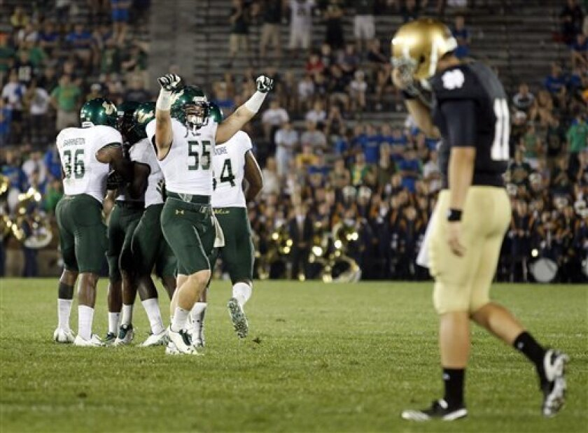 South Florida linebacker Michael Lanaris (55) celebrates a teammate interception of Notre Dame quarterback Tommy Rees, right, late in the fourth quarter of an NCAA college football game in South Bend, Ind., Saturday, Sept. 3, 2011. South Florida defeated Notre Dame 23-20. (AP Photo/Michael Conroy)