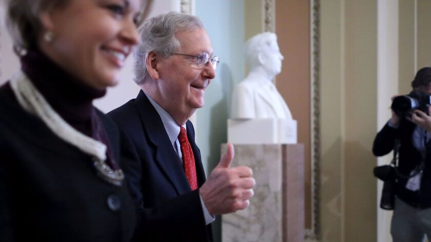 Senate Majority Leader Mitch McConnell (R-KY) gives a thumbs-up as he and his Director of Operations Stephanie Muchow head for the Senate floor in Washington on Dec. 1.