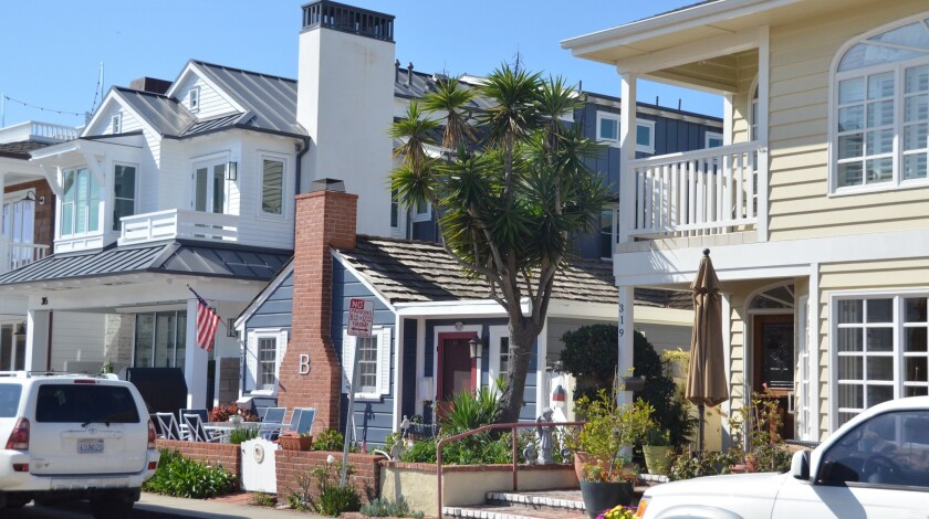 As more properties on Balboa Island have become permanent residences rather than vacation rentals, many people have made full use of the lots by replacing original beach cottages with big houses. Here is an example of an original cottage dwarfed by newer homes on both sides.