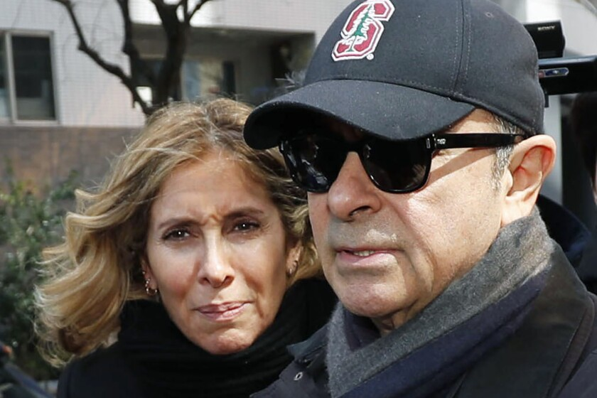 FILE - This March, 2019, file photo shows former Nissan Chairman Carlos Ghosn, right, and his wife Carole in Tokyo. Tokyo prosecutors issued an arrest warrant Tuesday, Jan. 7, 2020 for the wife of Nissan's former chairman, Carlos Ghosn, on suspicion of perjury. (Kyodo News via AP, File)