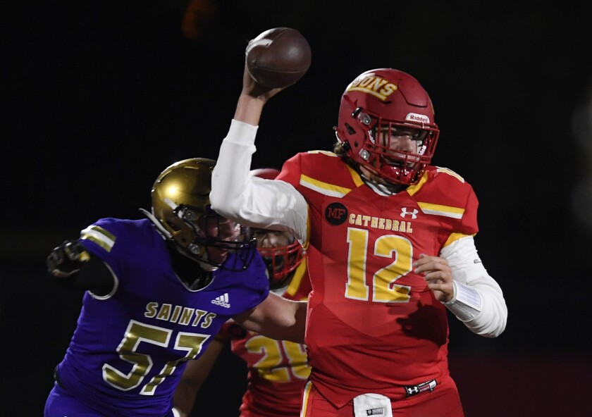 Cathedral Catholic's quarterback Charlie Mirer (12) looks to pass under pressure from St. Augustine's Christian Gaeta (57).