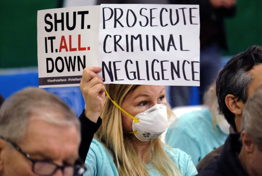 Tera Lecuona, a resident of the Porter Ranch area of Los Angeles, holds a protest sign during a hearing in Granada Hills over a gas leak at Southern California Gas Co.'s Aliso Canyon Storage Facility.