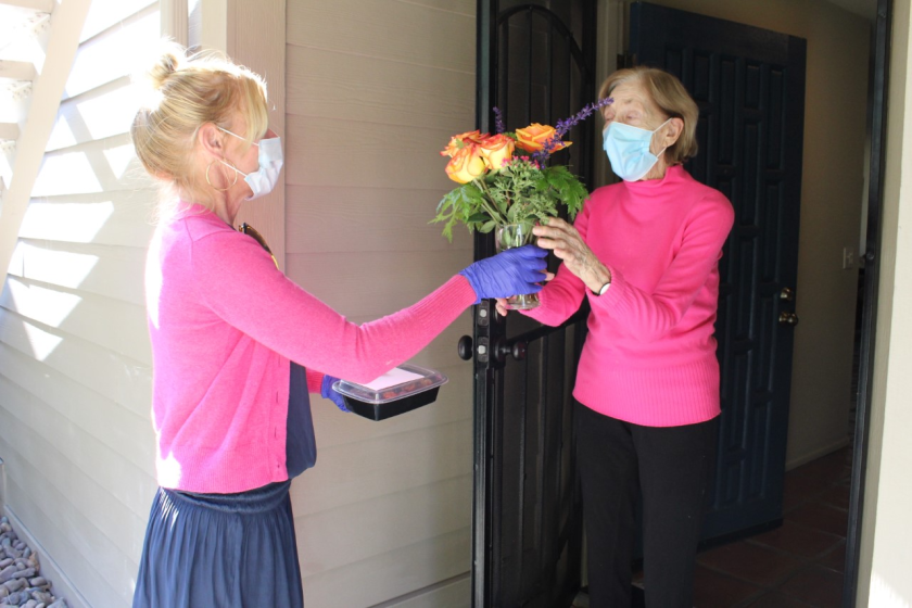 Del Mar Community Connections staff member Amanda Allen delivers Thanksgiving roses to Irene Russell.