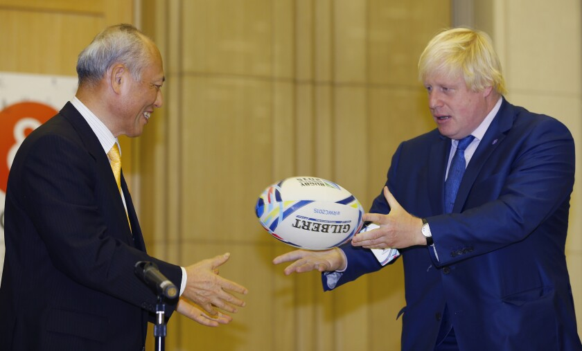 """FILE - In this Wednesday, Oct. 14, 2015 file photo, Mayor of London Boris Johnson, right, throws a rugby ball against Tokyo Gov. Yoichi Masuzoe during a press conference at Metropolitan Government Office in Tokyo. British Prime Minister Boris Johnson has come out in favor of England rugby fans singing """"Swing Low, Sweet Chariot"""" at a time when the historical context of the song is being reviewed. Johnson says there should not be """"any sort of prohibition on singing that song"""" and he would """"love"""" to hear the lyrics in full. The song is believed to have its roots in American slavery. (AP Photo/Shizuo Kambayashi, file)"""