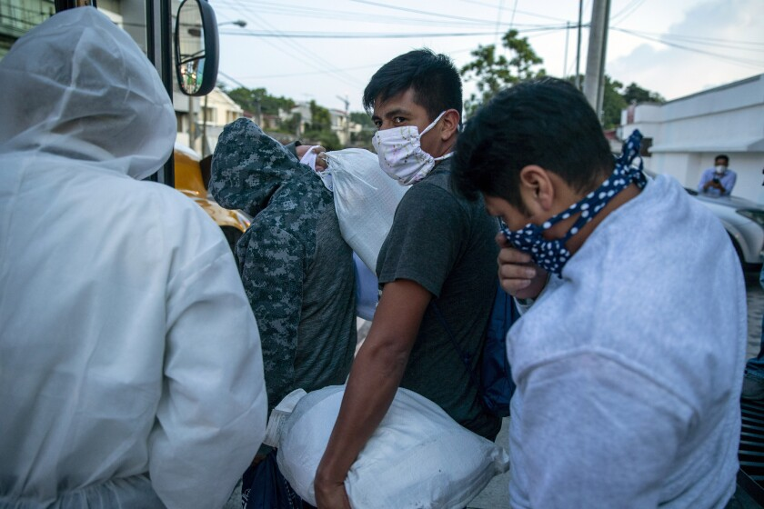 Guatemalans deported from the U.S., wearing a mask as a precaution against the spread of the new coronavirus, line up to board a bus after arriving at La Aurora airport in Guatemala City, Tuesday, June 9, 2020. The United States resumed deportation flights to Guatemala, nearly a month after the Central American country refused to accept them. (AP Photo/Moises Castillo)