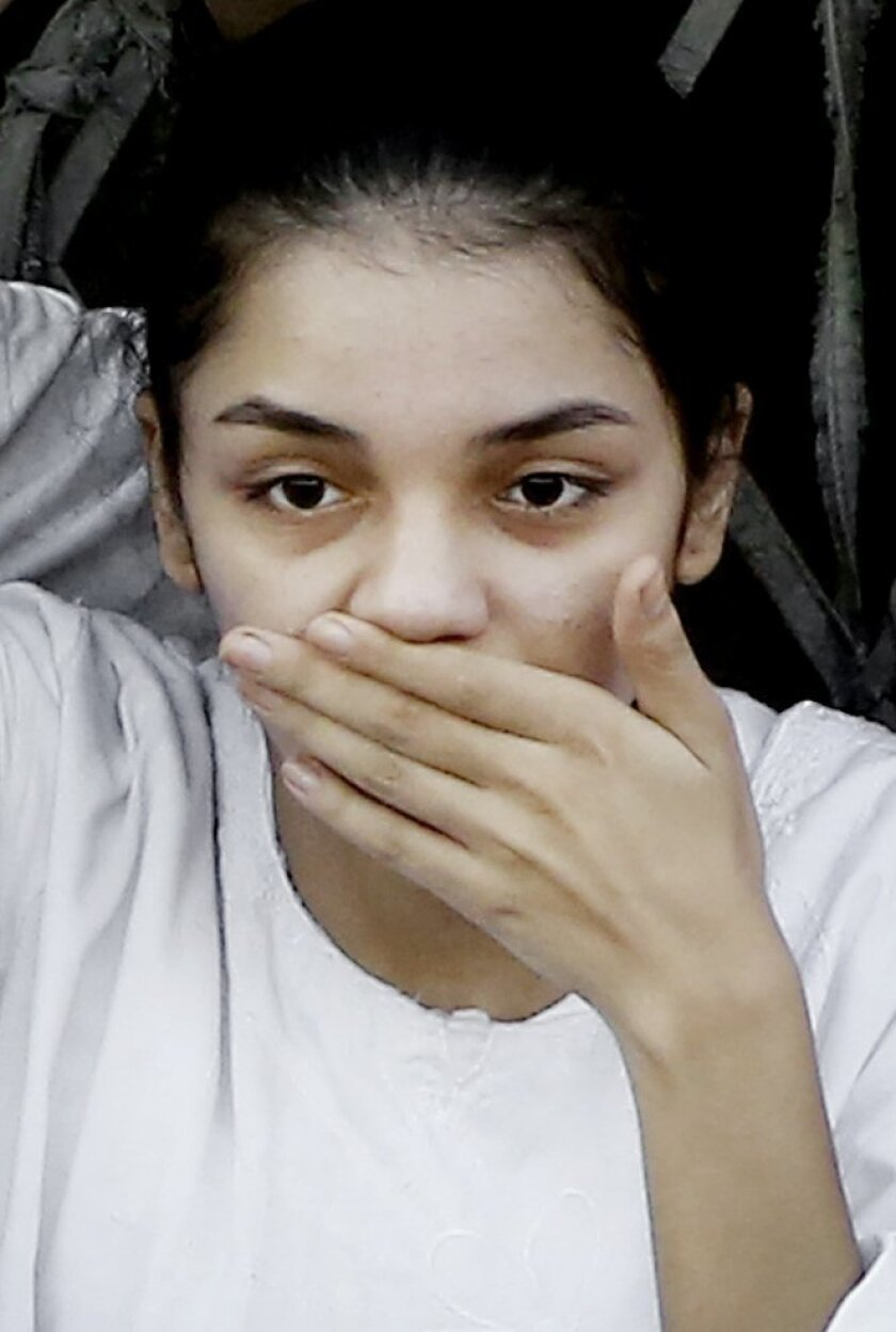 FILE - In this Thursday, Aug. 28, 2014 file photo, Egyptian activist Sanaa Seif, gestures after attending her father's, Ahmed Seif, funeral in Cairo, Egypt. When 22-year-old Sanaa was summoned for questioning on accusations of inciting protests, she refused to answer the investigating judge's quest