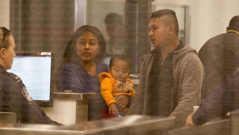 A family that waited in line to request asylum is interviewed in the first step of processing at the San Ysidro port of entry.