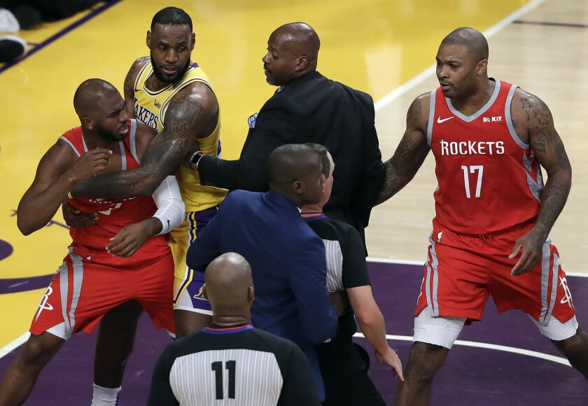 Rockets guard Chris Paul, left, is held back by Lakers forward LeBron James after Paul and Lakers guard Rajon Rondo (not pictured) exchanged punches.
