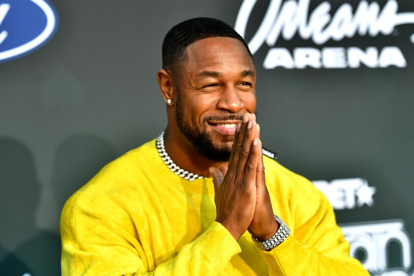 Singer Tank, in a yellow sweatshirt, smiles and presses his palms together