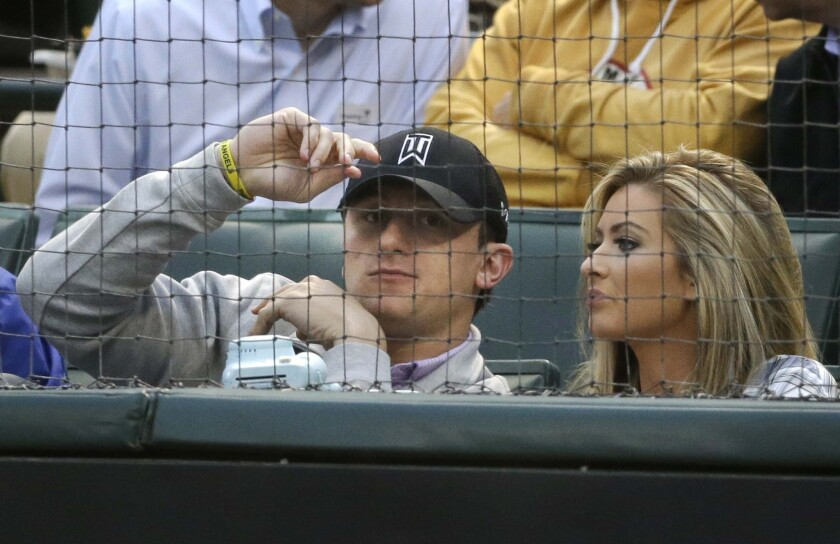 Johnny Manziel, left, sits with Colleen Crowley during a baseball game between the Angels and Texas Rangers in Arlington on April 14, 2015.