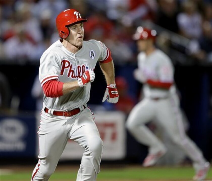 Philadelphia Phillies' Chase Utley, left, runs to first base after hitting a single to score teammates Cole Hamels, right, and Ben Revere, not pictured, in the fifth inning of an opening day baseball game against the Atlanta Braves, Monday, April 1, 2013, in Atlanta. (AP Photo/David Goldman)
