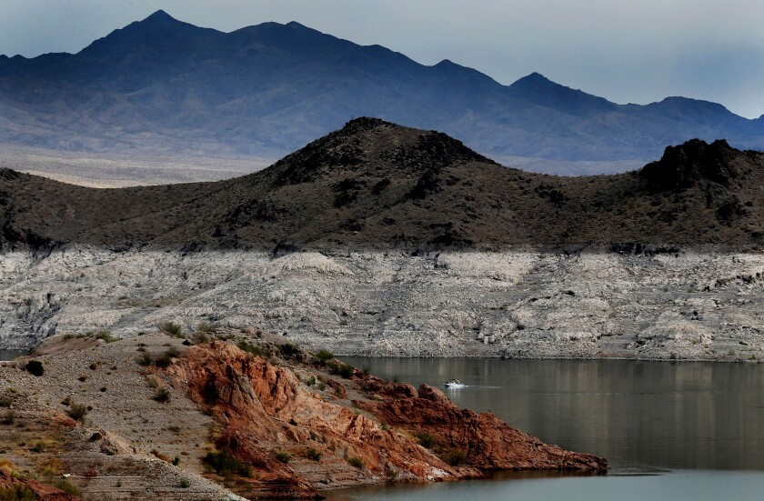 """A boat navigates Lake Mead, where a white """"bathtub ring"""" can be seen along the shore."""