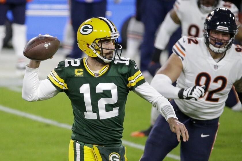El quarterback Aaron Rodgers (12), de los Packers de Green Bay, lanza en la primera mitad del duelo