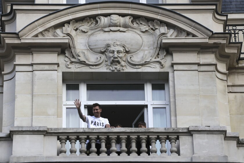 Argentinian soccer star Lionel Messi waves to supporters from his hotel balcony in Paris, Tuesday, Aug. 10, 2021. Lionel Messi finalized agreement on his Paris Saint-Germain contract and arrived in the French capital on Tuesday to complete the move that confirms the end of a career-long association with Barcelona. (AP Photo/Adrienne Surprenant)