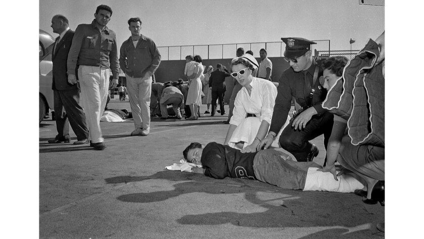 Jan. 31, 1957: Rescue workers treat Ken Smith, 13, in foreground, as others gather around additional