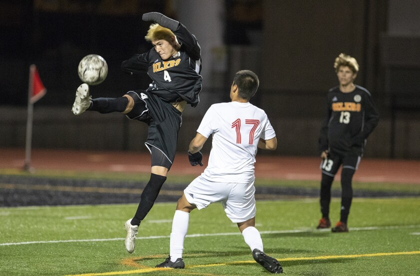 Huntington Beach's Dustin Herft leaps for a ball near Estancia's Marcos Arreola during a first round