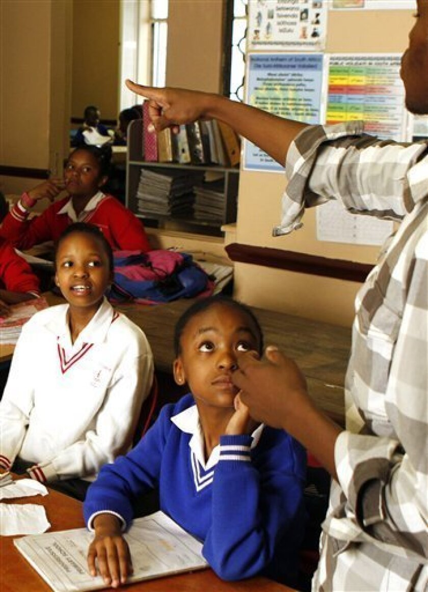 In this Oct. 28, 2010 photo, bible study teacher Micheal Mpubane, right, talks to students in a class at the Progressive Primary in Johannesburg. Progressive Primary is among an increasing number of such schools for poor South Africans underserved by a government that has struggled to close the gap