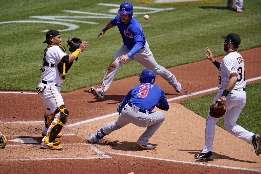 Pittsburgh Pirates first baseman Will Craig, right, tosses the ball to catcher Michael Perez.