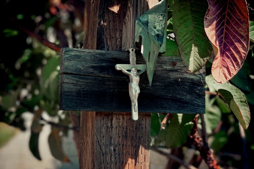 A small silver crucifix is seen nailed to a wooden post in the backyard of Alex Espinoza.