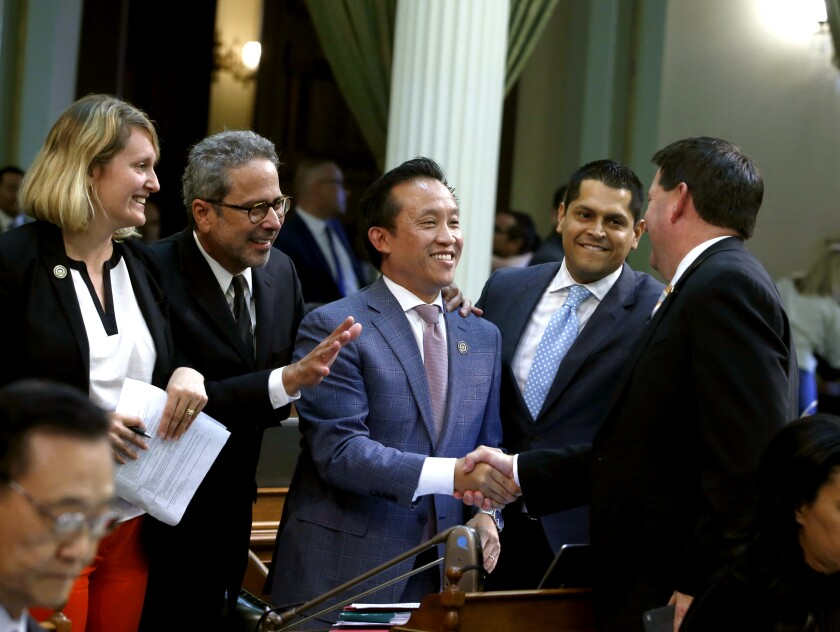 Assemblyman David Chiu, center, is congratulated after his rent-cap bill passed the Legislature