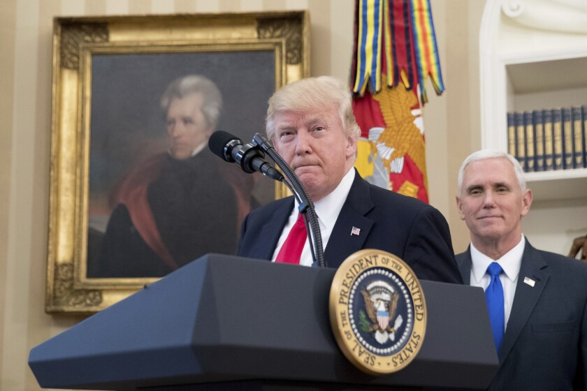 President Trump and Vice President Mike Pence at a lectern with the presidential seal