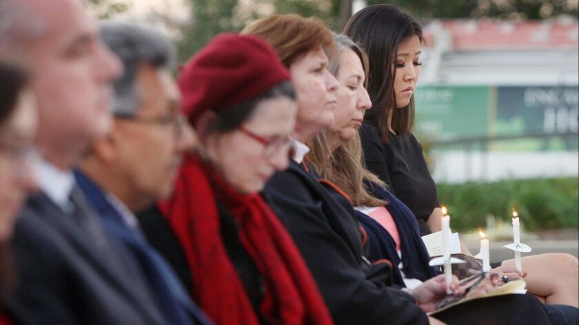 Attendees lower their heads during a prayer at Ascencia's memorial service for homeless people at Forest Lawn Memorial Park. The names of homeless people who died in 2018 were recognized by reading their names aloud.