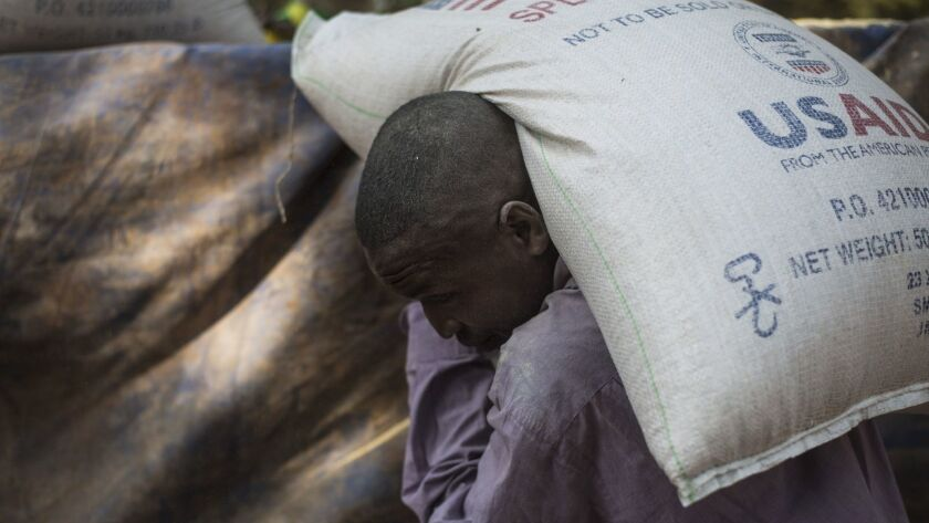 In 2013, a man carries a bag of food delivered by the U.S. Agency for International Development to a refugee camp in Bossangoa, Central African Republic.