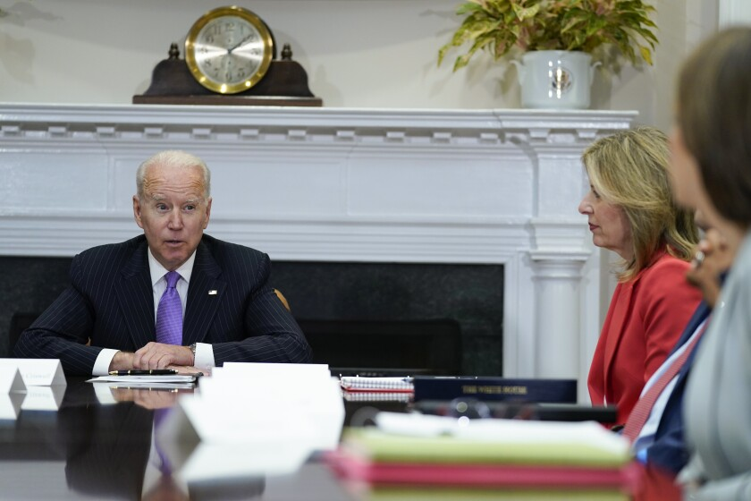 President Biden sits at a table with other people