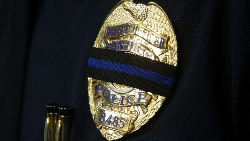 San Diego Police officer Max Verduzco wore a black band over his San Diego police officer's badge.