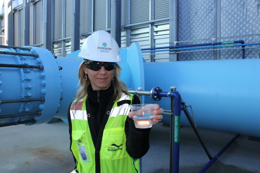 Poseidon spokeswoman Jessica Jones offers a visitor a cup of drinking water produced by the plant. The large blue water pipeline behind Jones carries the purified water out of the plant and into the pipeline that leads to the Water Authority aqueduct.