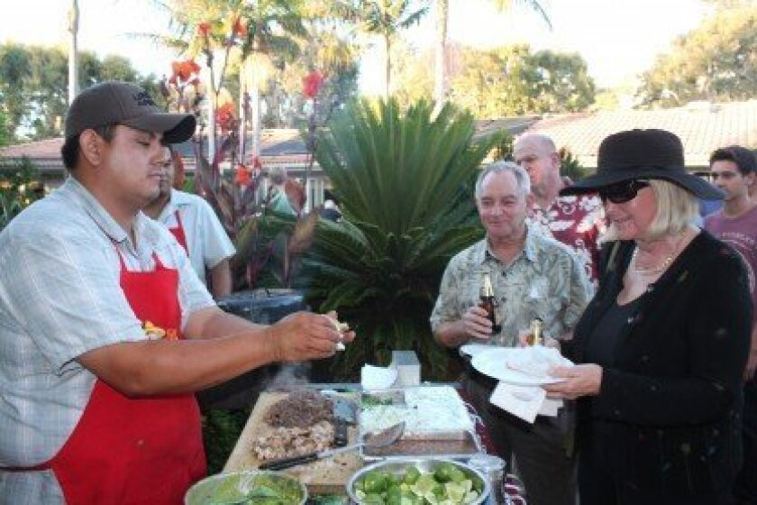 Nancy and Ross Rudolph wait while their tacos are prepared fresh on the grill by Tacos el Unico of Chula Vista.