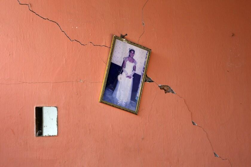 A portrait of a teenager hangs on a earthquake-damaged wall in Canoas, Ecuador.