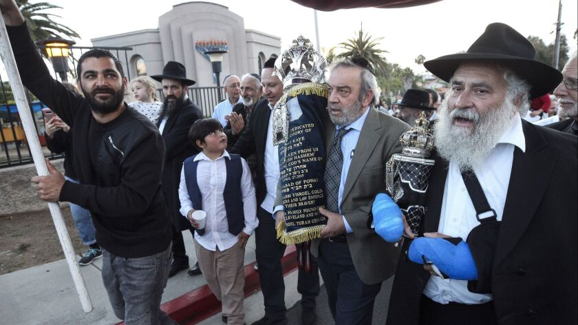Howard Kaye, the husband of Lori Kaye, carries the new Torah as Rabbi Yisroel Goldstein, right, and other members of the Chabad of Poway celebrate its completion.
