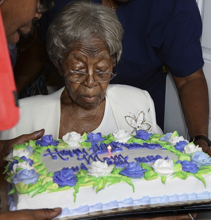 """Hester """"Granny"""" Ford at 111th birthday party blows out a candle on a cake decorated with flowers made of icing"""