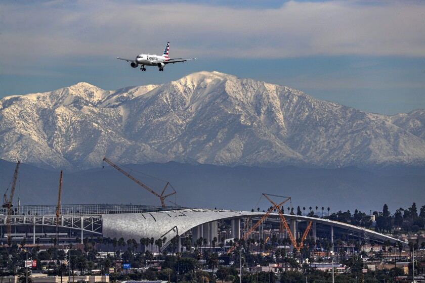 A plane approaches Los Angeles International Airport on Saturday against the backdrop of snow-covered mountains and over SoFi Stadium, which will be the new home of the Los Angeles Rams and Chargers when it opens next summer.