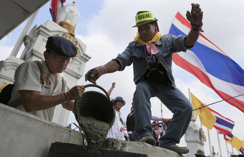 Anti-government protesters pour cement on concrete barriers to seal the gate of the prime minister's office of government house during a rally in Bangkok, Thailand, Monday, Feb. 17, 2014. Suthep Thaugsuban led hundreds of protesters to surround the government house after hearing that Prime Minister Yingluck Shinawatra will this week return to work at her office. (AP Photo/Wason Wanichakorn)