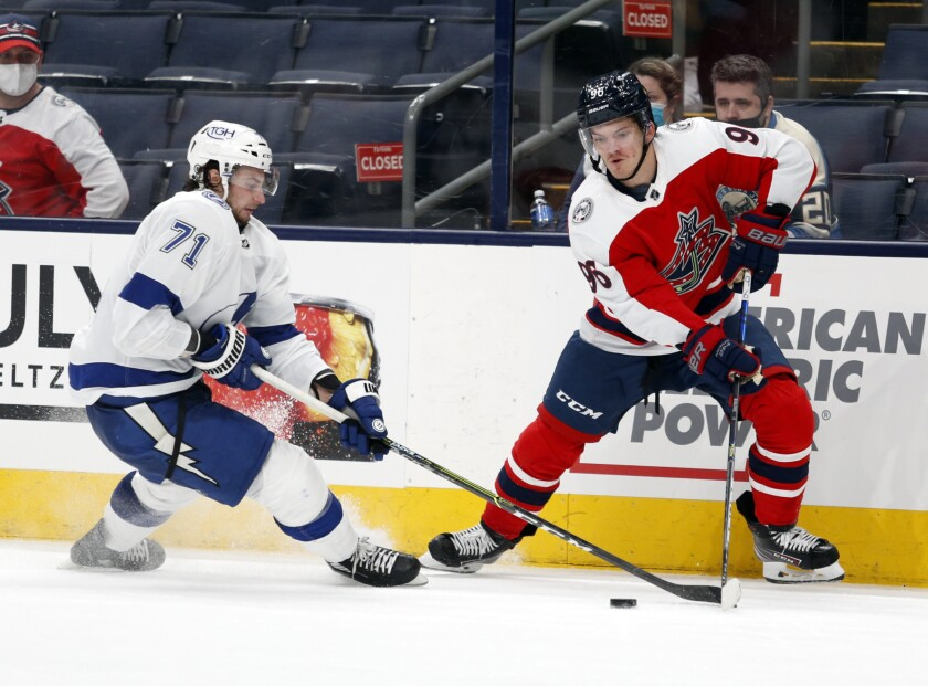 Columbus Blue Jackets forward Jack Roslovic, right, reaches for the puck against Tampa Bay Lightning forward Anthony Cirelli during the second period of an NHL hockey game in Columbus, Ohio, Tuesday, April 6, 2021. (AP Photo/Paul Vernon)