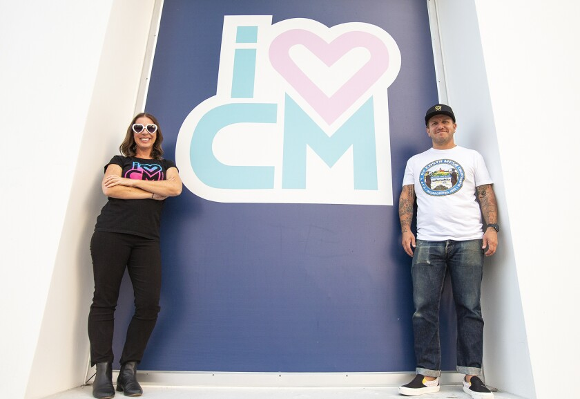 Erin Huffstutter, left, and Dean Tompkins  in front of the I Heart Costa Mesa sign outside of Triangle Square.