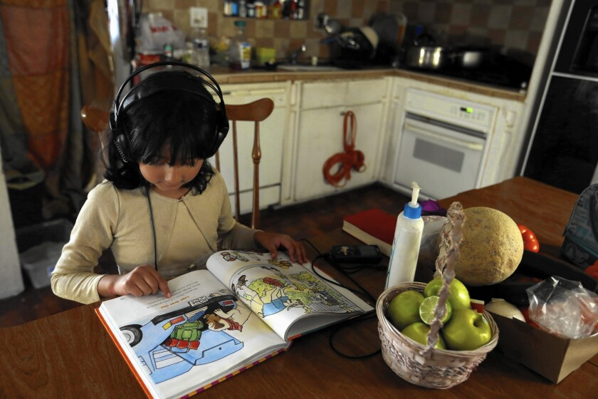 Alessandra Alamilla, 7, reads at the kitchen table in her home in San Bernardino. All of her siblings are focused on academics, and they all want to help their hardworking parents.