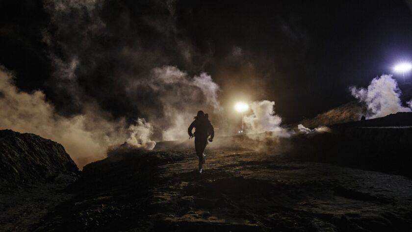 Migrants run as tear gas is thrown by U.S. border officers to the Mexican side of the border fence after the migrants had climbed a fence to try to get to San Diego from Tijuana on Tuesday.
