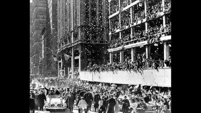 Astronaut John Glenn in car at left, the first American to orbit the Earth, got a massive ticker tape parade welcome along lower Broadway on March 1, 1962. A partly constructed building at right served as a grandstand for a cheering crowd. Sitting beside the astronaut is Annie Glenn, his wife.