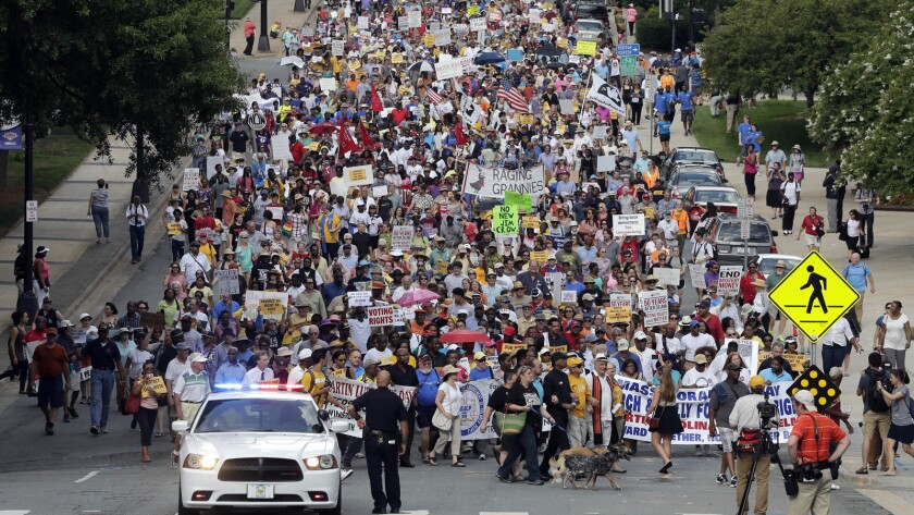 Demonstrators march through the streets of Winston-Salem, N.C., after the beginning of a federal voting rights trial.