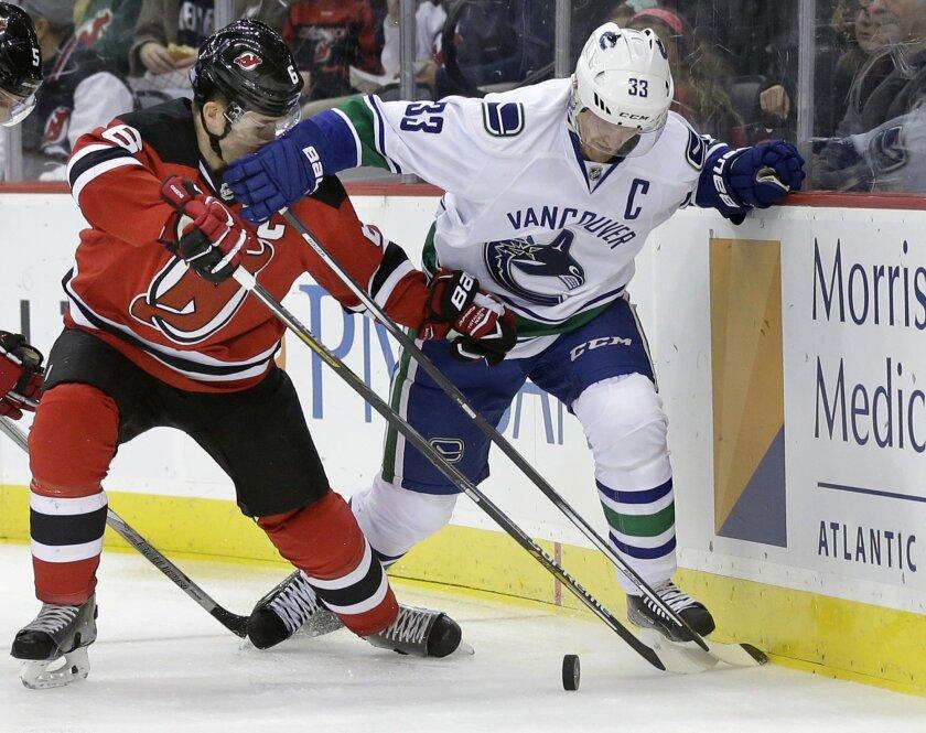 Vancouver Canucks center Henrik Sedin (33) blocks New Jersey Devils defenseman Andy Greene over the puck during the first period of an NHL hockey game Sunday, Nov. 8, 2015, Newark, N.J. (AP Photo/Mel Evans)