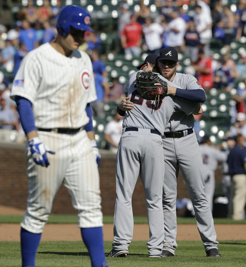 Atlanta Braves third baseman Chris Johnson, center, celebrates with first baseman Freddie Freeman as Chicago Cubs' Anthony Rizzo walks off the field after the Braves defeated the Cubs 10-7 in a baseball game in Chicago, Sunday, July 13, 2014. (AP Photo/Nam Y. Huh)