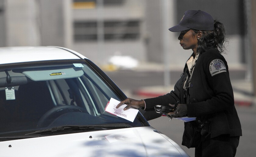 A parking enforcement officer tickets a car parked in an area scheduled for street sweeping.