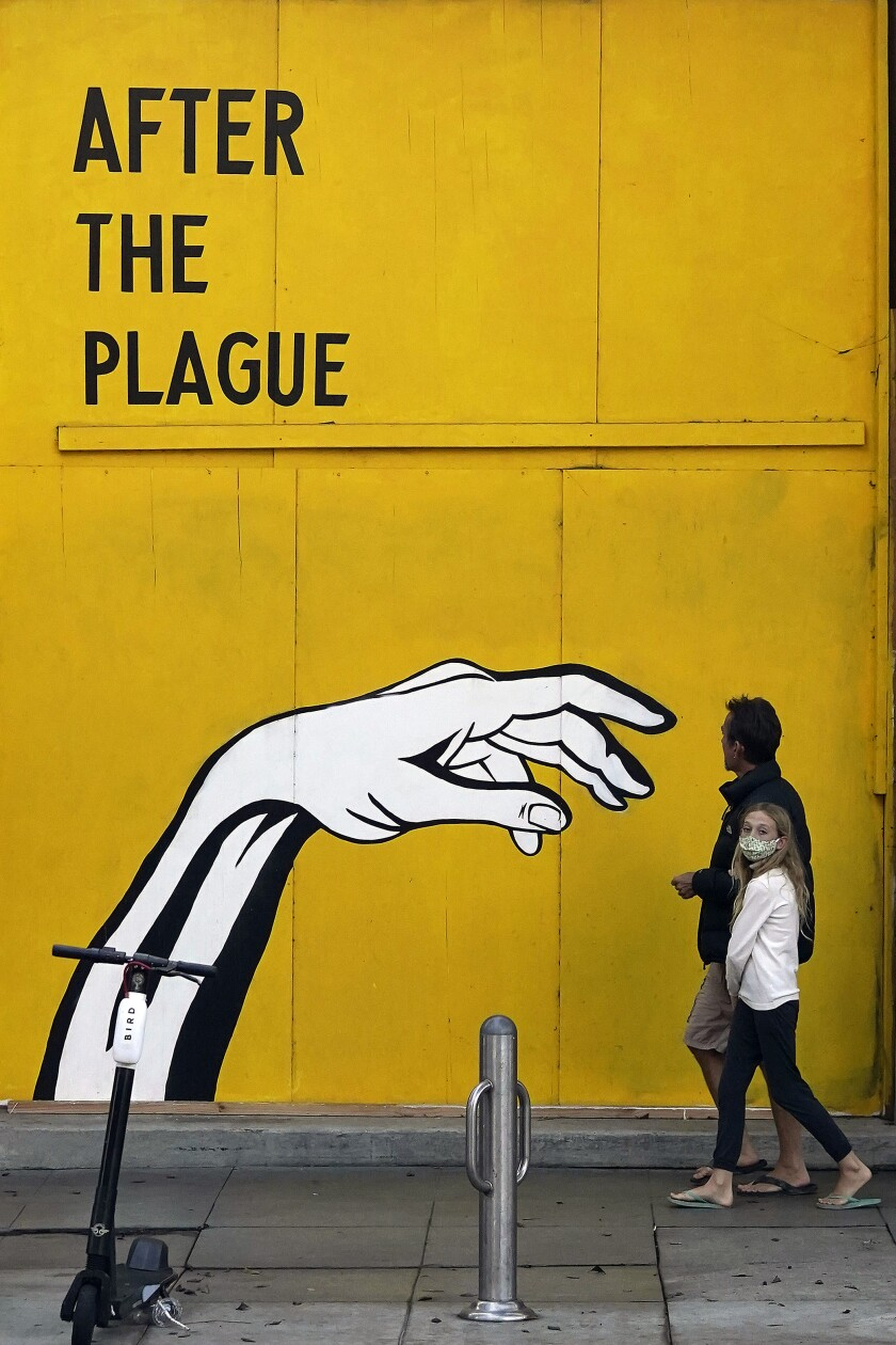 Pedestrians walk past a COVID-19-themed mural outside a boarded up business Monday, Nov. 23, 2020, in Santa Monica, Calif. (AP Photo/Marcio Jose Sanchez)