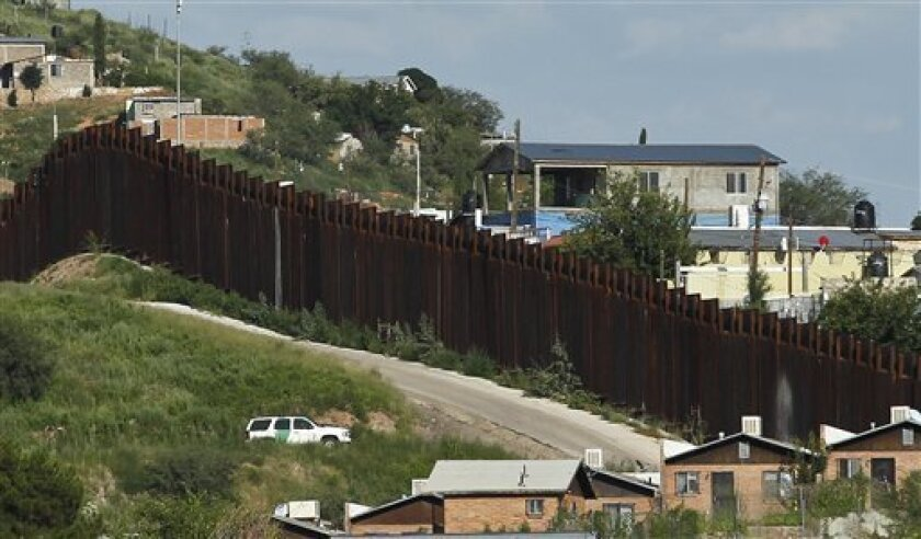 In this photo taken Thursday, Aug. 9, 2012, A U.S. Border Patrol vehicle keeps watch along the border fence in Nogales, Ariz.  A U.S. Border Patrol agent opened fire on a group of people throwing rocks from across the Mexican border, killing a teenage boy and eliciting outrage from the Mexican gove