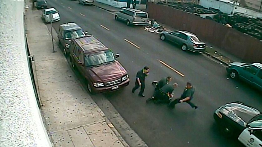 An image from a 2014 surveillance video shows officers surrounding a man on the ground in South Los Angeles.